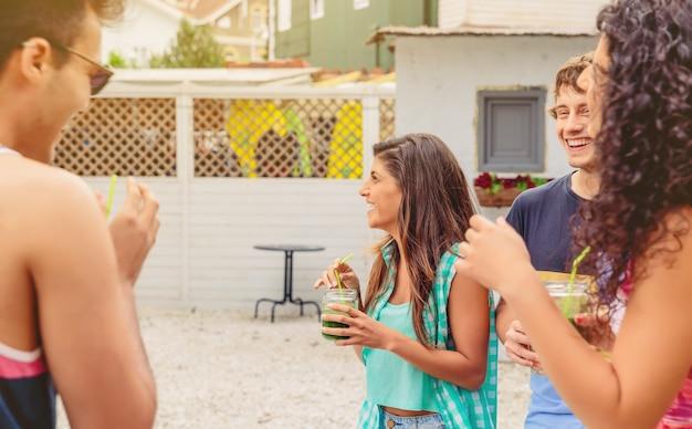 Groupe de jeunes gens heureux avec des boissons saines s'amusant dans une fête d'été en plein air. concept de mode de vie des jeunes.