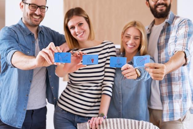 Groupe de jeunes gens heureux joyeux tenant des autocollants de note bleue avec des images clipart pour une entreprise prospère.
