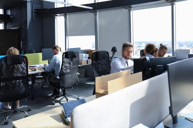Groupe de jeunes gens modernes en tenue de soirée utilisant des technologies modernes tout en travaillant dans le bureau de création.