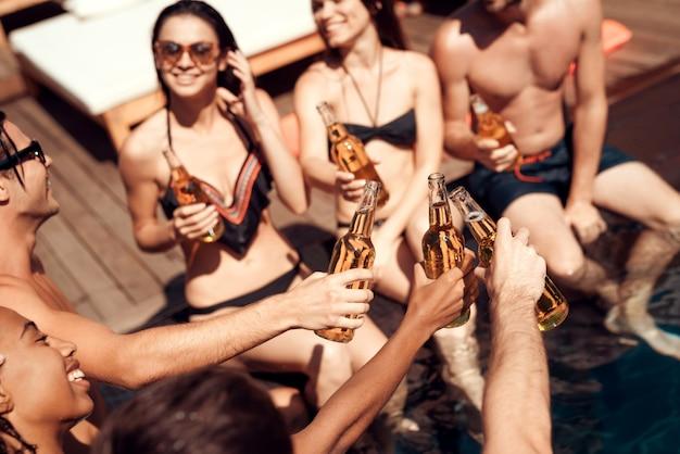Groupe de jeunes gens souriants tenant des bouteilles de bière