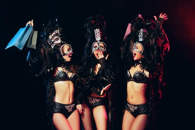 Le groupe de jeunes heureuses souriantes belles danseuses avec des robes de carnaval posant avec des sacs à provisions sur fond de studio noir