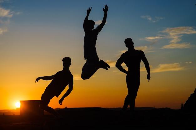 Groupe de jeunes heureux sautant sur le toit avec coucher de soleil