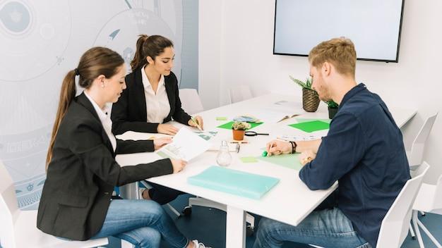 Groupe de jeunes hommes d'affaires travaillant sur le lieu de travail
