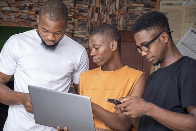 Groupe de jeunes hommes africains discutant d'un projet tout en utilisant leur ordinateur portable et leurs téléphones
