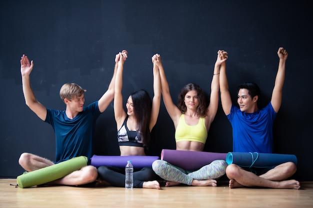 Groupe de jeunes hommes et femmes assis sur le mur en attente de cours de yoga au gymnase