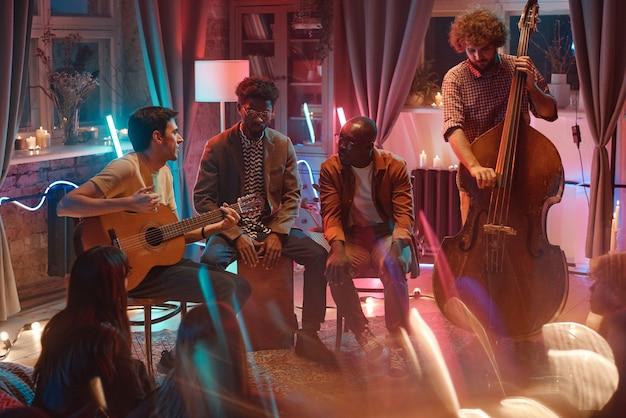 Groupe de jeunes hommes jouant dans le club à l'aide d'instruments de musique