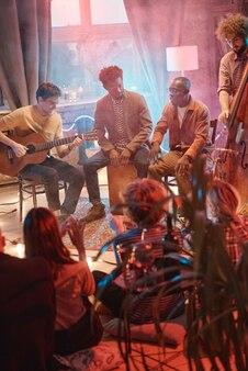 Groupe de jeunes hommes jouant sur des instruments de musique jouant pour leurs amis en studio