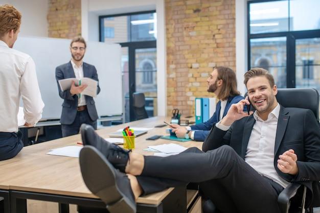 Groupe de jeunes hommes joyeux en costumes bavardant au bureau après présentation dans une atmosphère calme