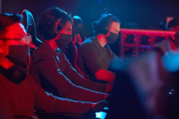 Groupe de jeunes hommes masqués jouant à des jeux informatiques dans une pièce sombre en club informatique