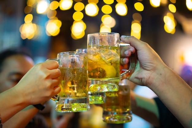 Groupe de jeunes hommes portant un toast dans une discothèque