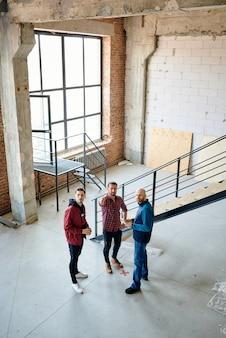 Groupe de jeunes ingénieurs ou entrepreneurs debout par escalier tout en discutant de la qualité du travail des constructeurs en construction inachevée