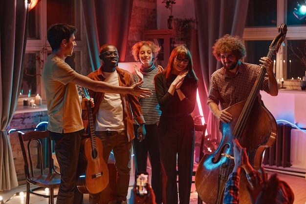 Groupe de jeunes avec des instruments jouant sur le concert dans la boîte de nuit et parlant à leurs fans