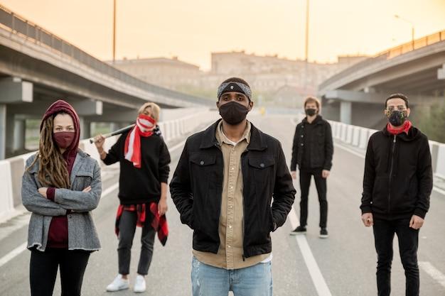 Groupe de jeunes interraciaux masqués debout dans une rue vide de la ville et revendiquant leurs droits au lever du soleil