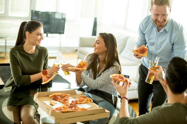 Groupe de jeunes joyeux mangeant des pizzas dans la chambre et s'amusant