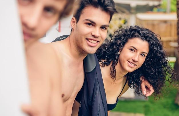 Groupe de jeunes en maillot de bain avec des planches de surf s'amusant à l'extérieur par une journée d'été. mise au point sélective sur la femme en arrière-plan.