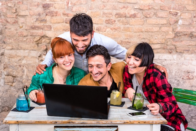 Groupe de jeunes meilleurs amis hipster avec ordinateur en studio alternatif urbain