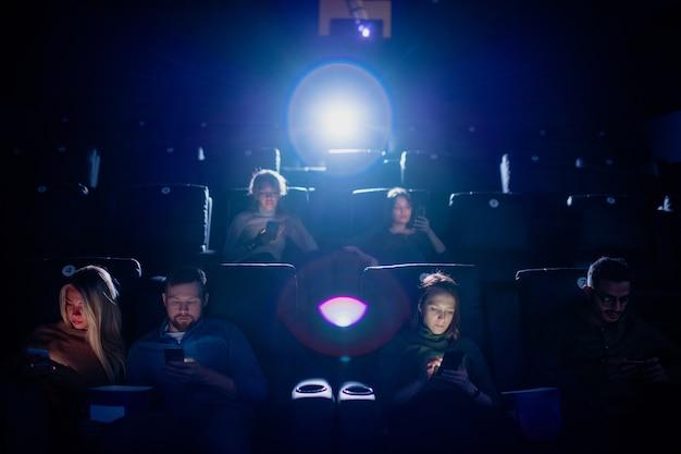 Groupe de jeunes mobiles défilant dans leurs smartphones dans un cinéma sombre en attendant le début du film