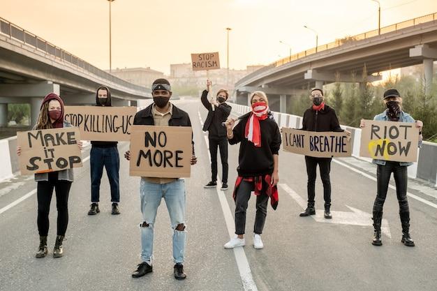 Groupe de jeunes multiethniques portant des masques en tissu debout sur la route tout en protestant dans la rue