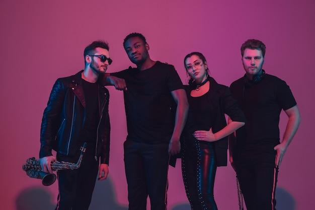 Un groupe de jeunes musiciens multiethniques a créé un groupe, dansant à la lumière du néon sur fond rose. concept de musique, passe-temps, festival, bien-être. hôte joyeux, danseur, chanteur, guitariste, saxophoniste.