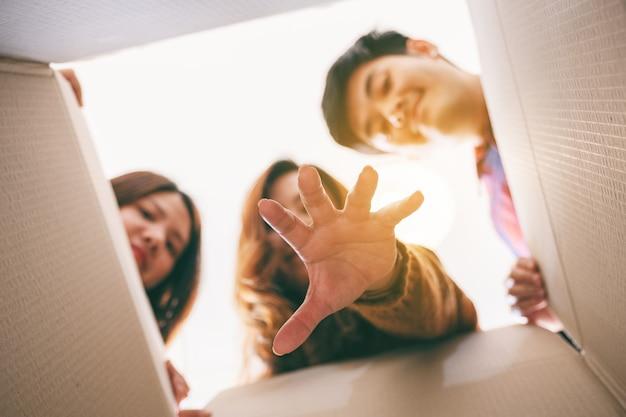 Groupe de jeunes ouvrant et saisissant un cadeau dans la boîte