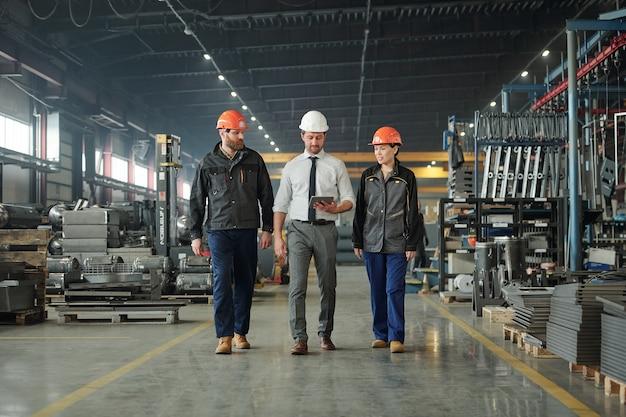 Groupe de jeunes ouvriers d'usine contemporains dans des casques discutant des données techniques tout en marchant le long de l'atelier