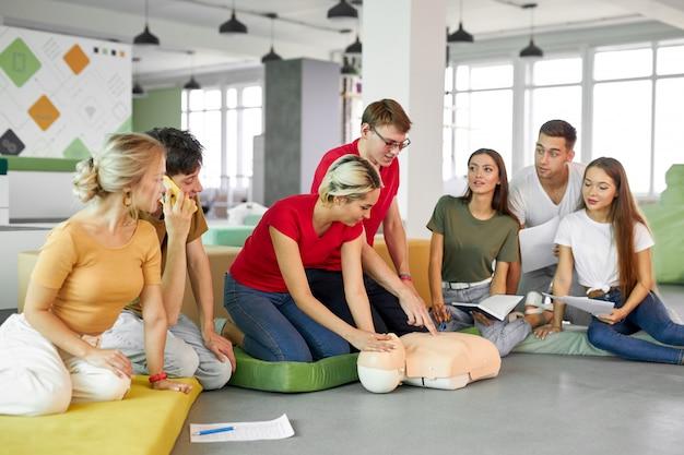 Groupe de jeunes personnes diverses pratiquant la formation aux premiers secours à la main