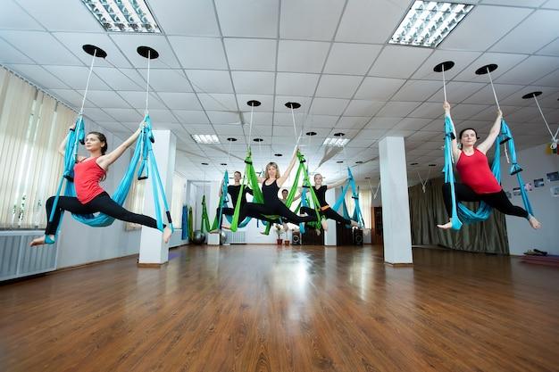 Groupe de jeunes pratiquant le yoga sur hamac au club de santé. fitness, étirement, équilibre