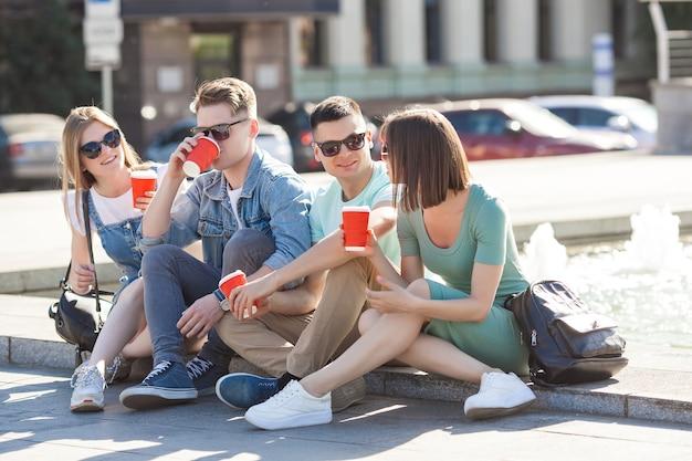 Groupe de jeunes près de la fontaine, boire du café et s'amuser. amis se détendre à l'extérieur.