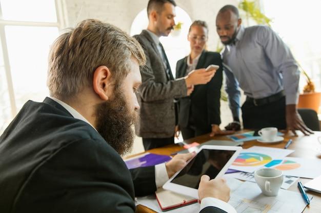 Groupe de jeunes professionnels ayant une réunion. divers groupes de collègues discutent des nouvelles décisions, des plans futurs et de la stratégie. réunion et lieu de travail créatifs, affaires, finances, travail d'équipe.