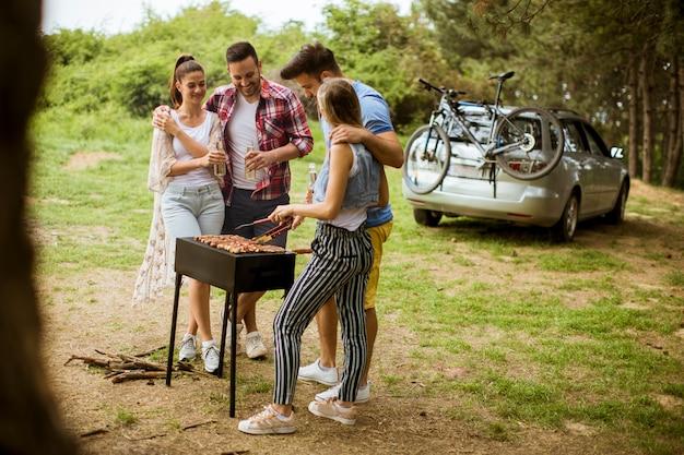 Groupe de jeunes profitant d'un barbecue dans la nature
