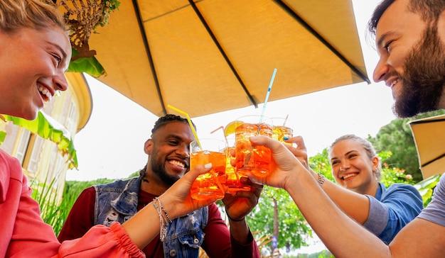Groupe de jeunes s'amusant à l'extérieur dans un bar avec des boissons en été - des amis applaudissent avec un cocktail et sourient en riant les uns avec les autres
