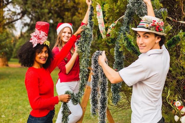Groupe de jeunes souriant tout en décorant le sapin de noël