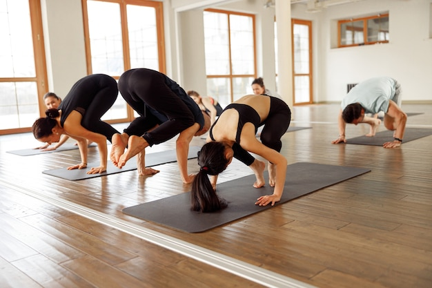 Groupe de jeunes sportifs attirants pratiquant une leçon de yoga avec instructeur. entraînez-vous à l'activité physique en classe de studio moderne, concept de bien-être.