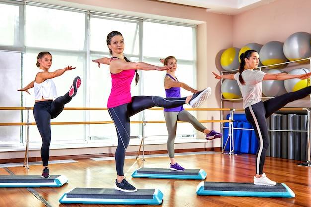Groupe de jeunes sportifs attrayants pratiquant la leçon de yoga avec instructeur