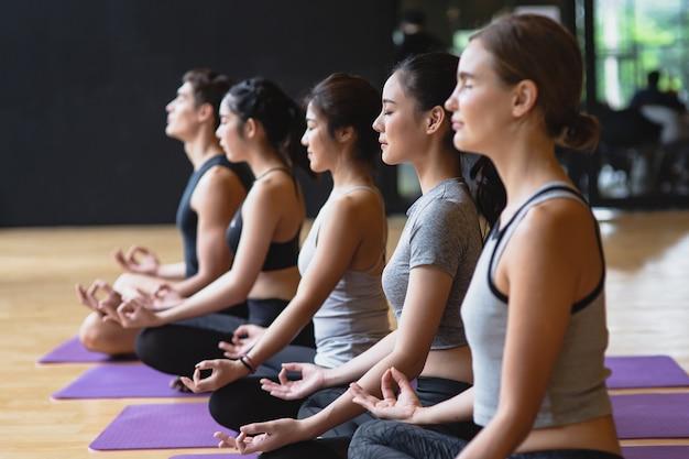 Groupe de jeunes sportifs pratiquant des cours de yoga faisant de la méditation lotus pose avec copie espace