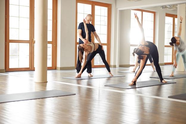 Groupe de jeunes sportifs pratiquant une leçon de yoga avec instructeur. cours de yoga. concept de remise en forme, d'entraînement, de sport, de yoga et de personnes.