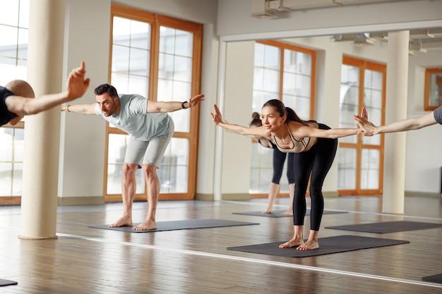 Groupe de jeunes sportifs pratiquant une leçon de yoga avec instructeur. cours de yoga en studio.