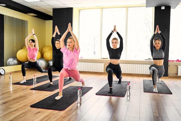 Groupe de jeunes sportifs pratiquant la leçon de yoga