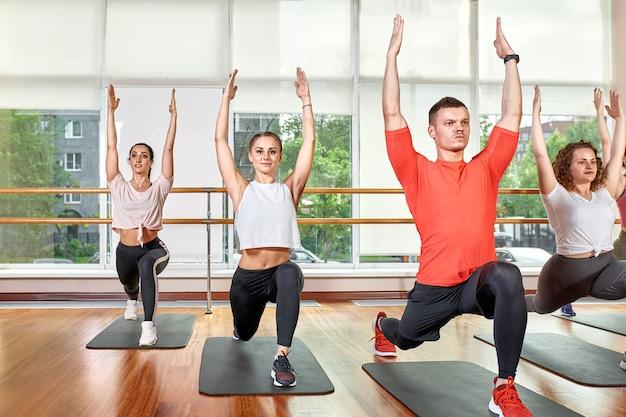 Groupe de jeunes sportifs en tenue de sport, dans une salle de fitness