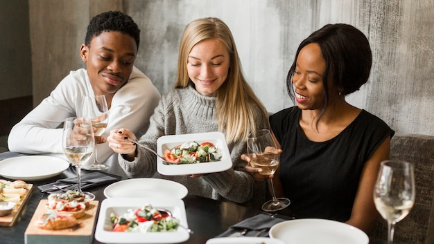 Groupe de jeunes en train de dîner ensemble