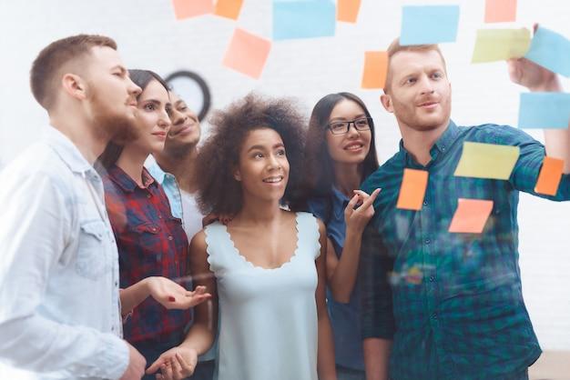 Un groupe de jeunes travailleurs regardent le verre avec des autocollants.