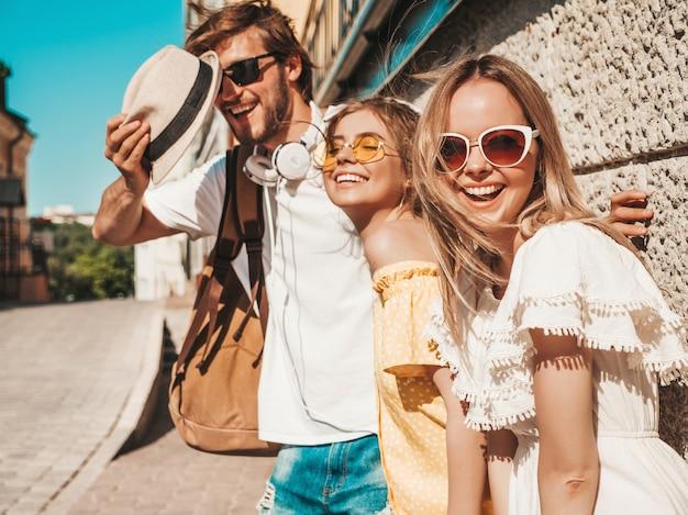 Groupe de jeunes trois amis élégants posant dans la rue. homme de mode et deux jolies filles vêtues de vêtements d'été décontractés. sourire, modèles, amusant, lunettes soleil., gai, femmes, et, type, dehors
