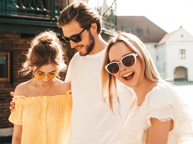 Groupe de jeunes trois amis élégants posant dans la rue. homme de mode et deux jolies filles vêtues de vêtements d'été décontractés. sourire, modèles, amusant, lunettes soleil., gai, femmes, et, type, devenir fou