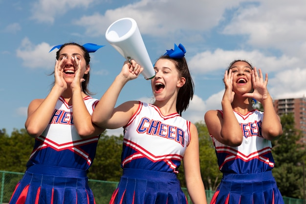 Groupe de jolis adolescents en uniforme de pom-pom girl