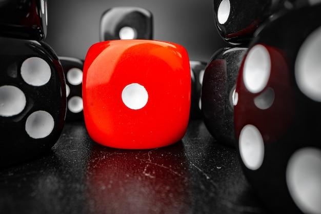 Groupe de jouer à des cubes de dés sur une surface noire, macro