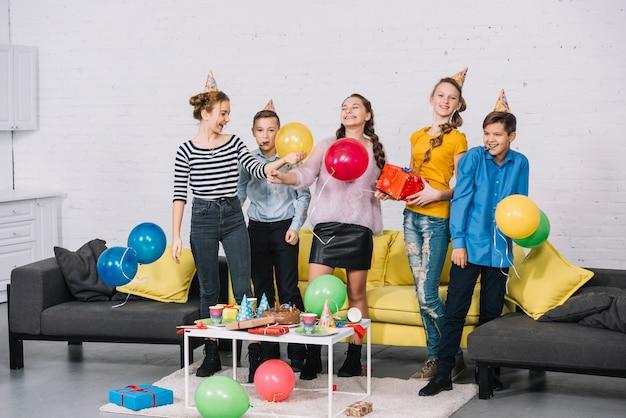 Groupe de joyeux amis célébrant la fête d'anniversaire à la maison