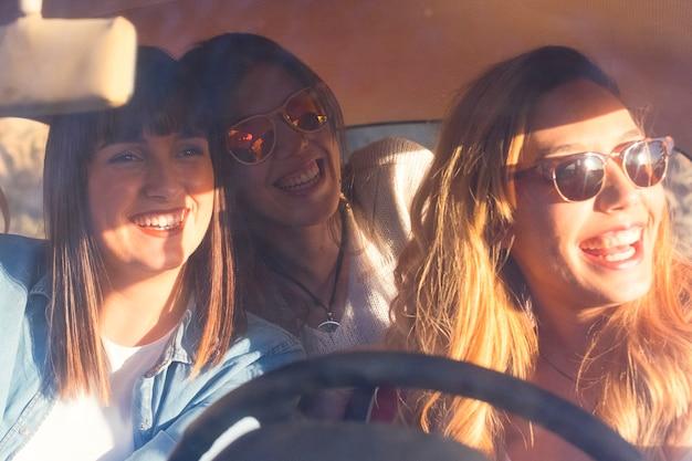 Groupe de joyeux amis ensoleillés heureux et beaux jeune femme à l'intérieur d'une voiture profiter et s'amuser ensemble voyager et conduire