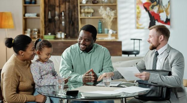 Groupe de joyeux couple ethnique avec fille et agent barbu adulte se réunissant à table pour discuter de l'hypothèque immobilière
