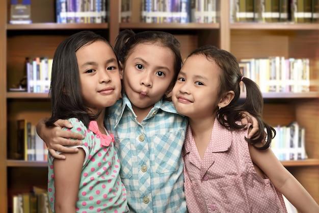 Groupe de joyeux enfants asiatiques jouant et debout ensemble