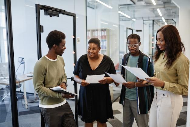 Groupe de joyeux hommes d'affaires afro-américains ayant une courte réunion dans le couloir du bureau pour discuter ...